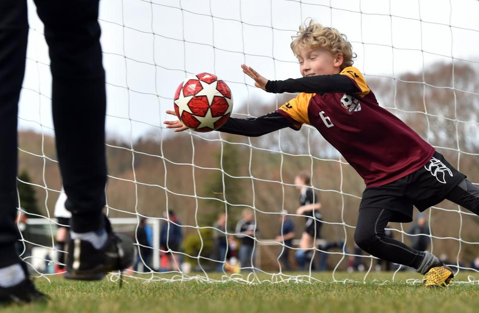 Thomas O'Neil (9), from the Maori Hill Football Club, practises before a game yesterday.