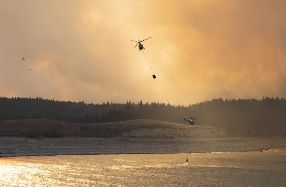 Smoke rises from the blaze as helicopters fight the fire near Twizel. Photo: Murray Eskdale