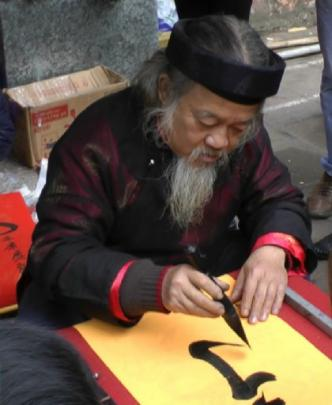 """People queue to have bearded calligraphers inscribe traditional """"parallel sentences""""."""