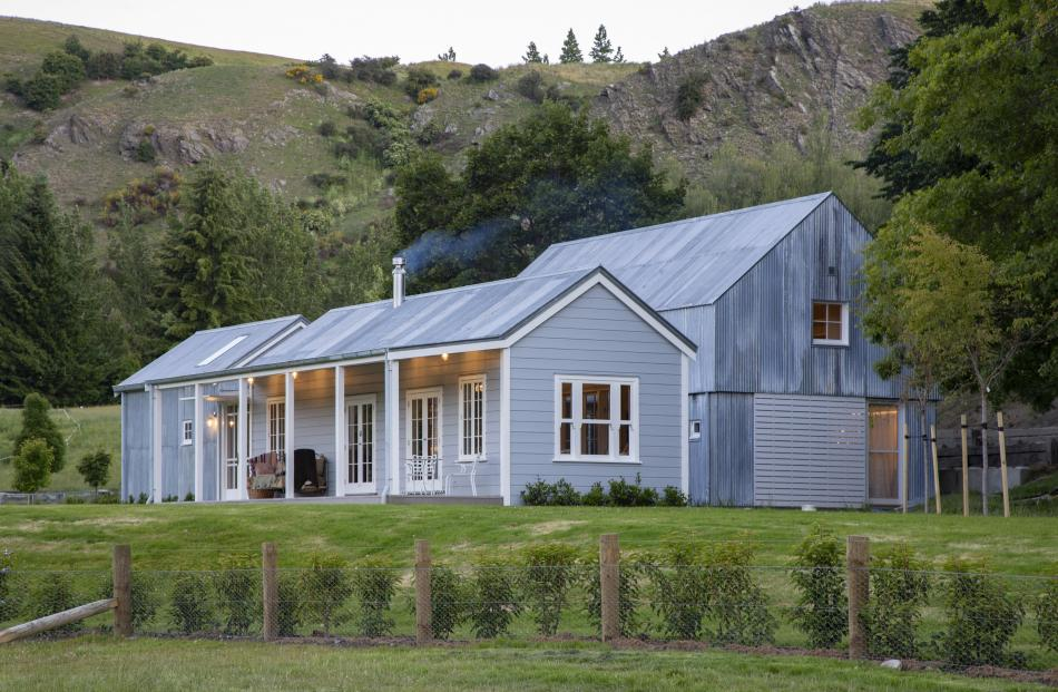 A restored weatherboard cottage, containing the main living areas,  sits in front of a new, two...