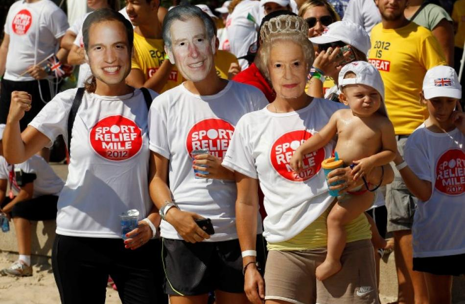 Fans wearing masks depicting members of Britain's royal family wait for Prince Harry to arrive at...