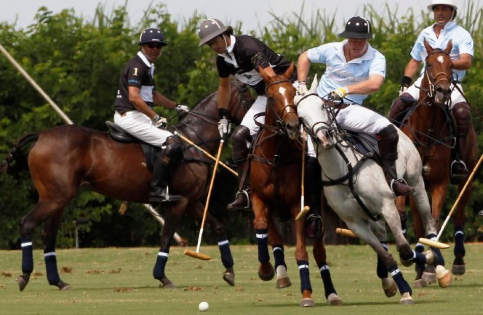 Nacho Figueras of Argentina (2nd L) is challenged by Prince Harry (2nd R) during their polo match...