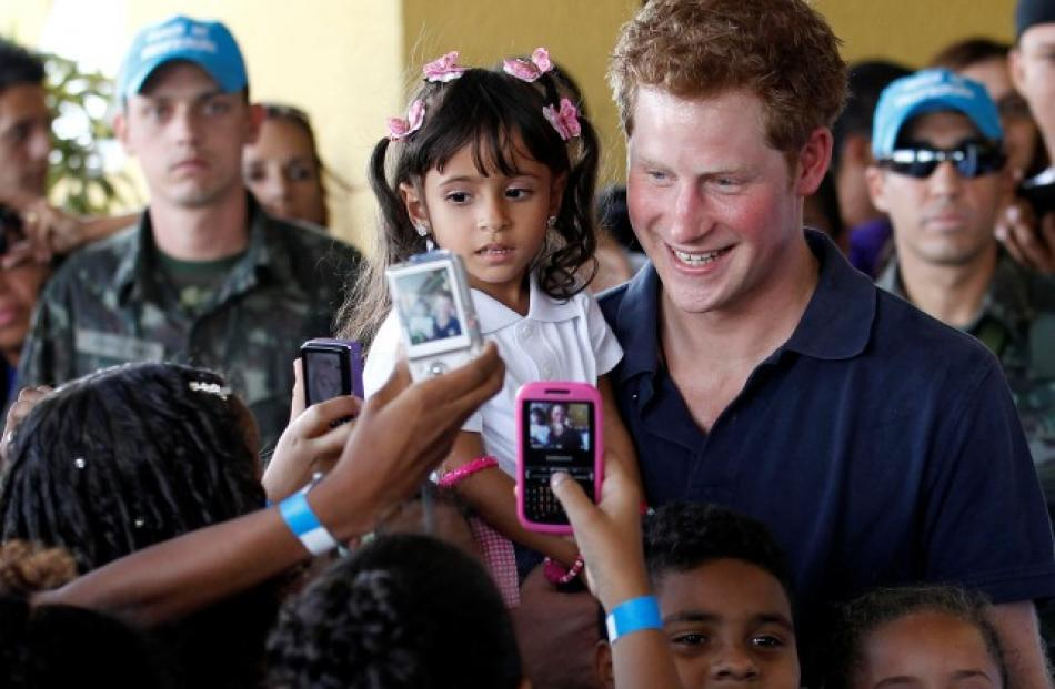 Prince Harry holds Mayara Pereira, 3, as he visits the occupied community of Complexo do Alemao...