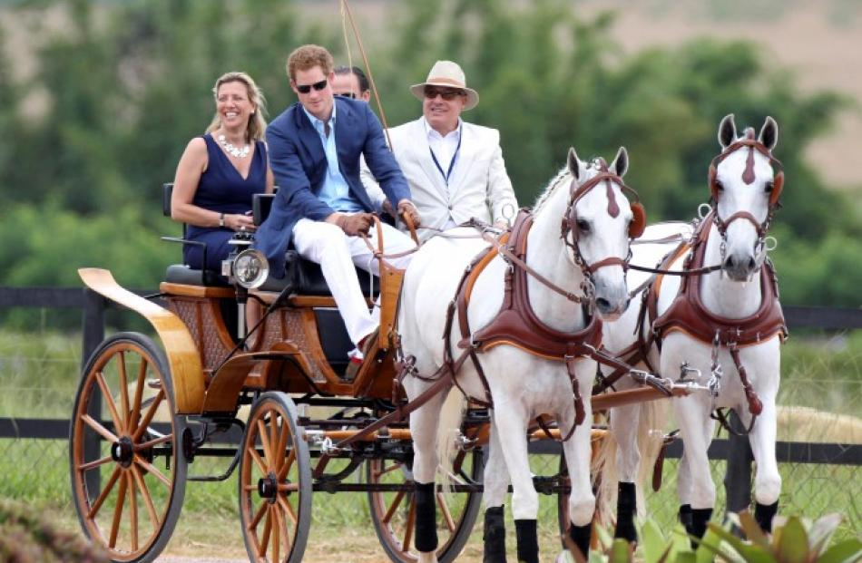 The prince (2nd L) drives a horse carriage as he arrives to play polo at a farm in Campinas....