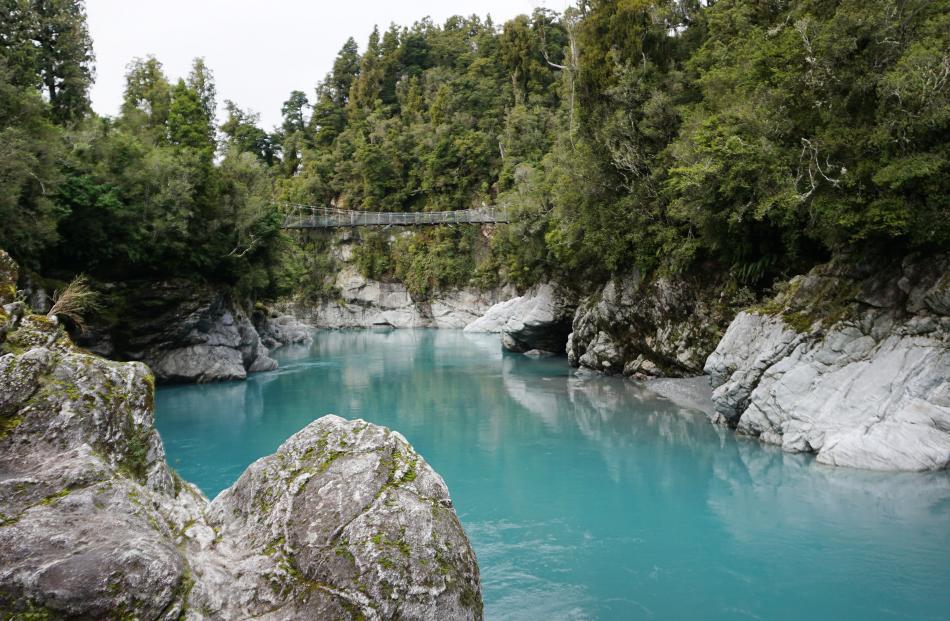The water is a deep turquoise as it runs through Hokitika Gorge.