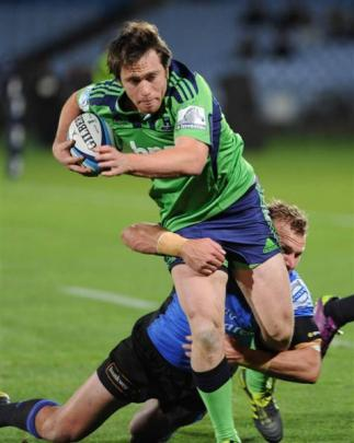 Ffullback Ben Smith, wearing the controversial green jersey, tries to beat a Force defender last...