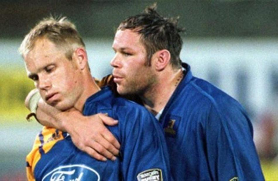Josh Kronfeld consoles Jeff Wilson after the semifinal loss to the Crusaders in 2000.