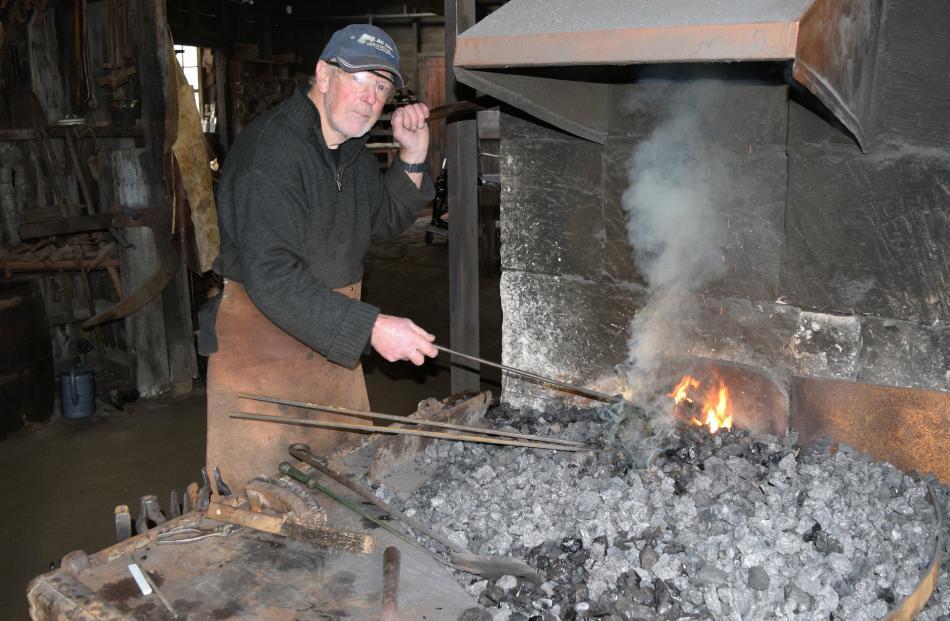 Nicol's Blacksmith Shop volunteer John Stannard heats metal in a forge in Duntroon.