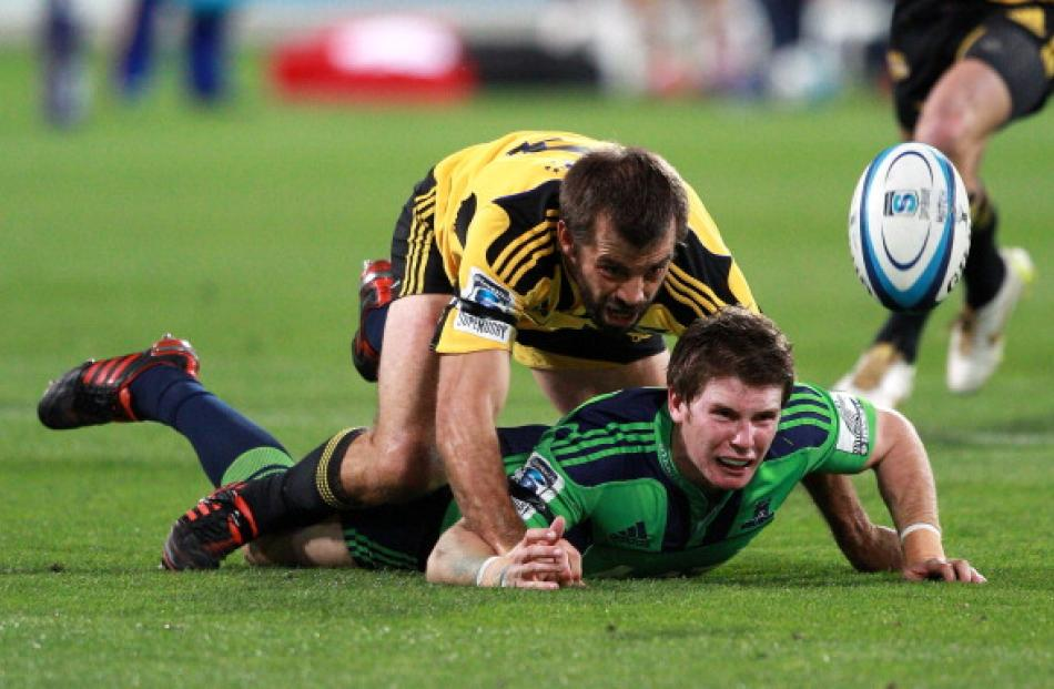 Conrad Smith tackles Highlanders first five Colin Slade. (Photo by Hagen Hopkins/Getty Images)