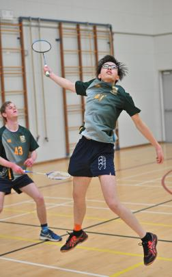Bayfield High School's Tony Lin stretches to play a shot in the badminton as Jack Campbell...