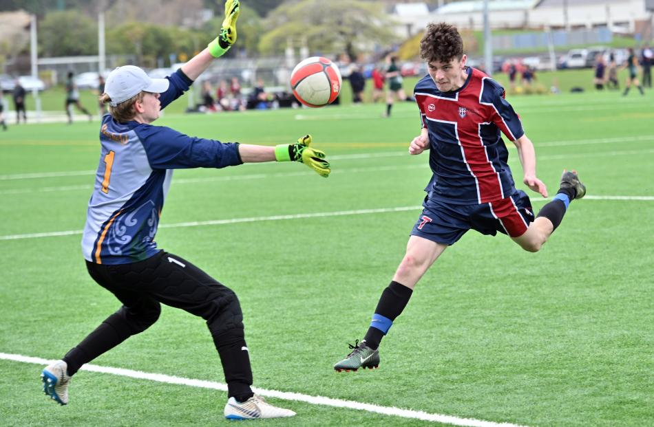 Kavanagh College's Cormac Kelly scores in the boys football as Bayfield High School goalkeeper...
