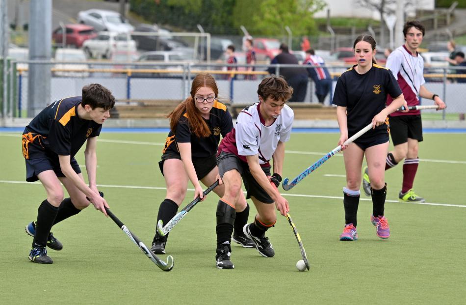 Logan Park High School's Liam Black controls the ball as Tokomairiro players Nathan Davie, Meg...