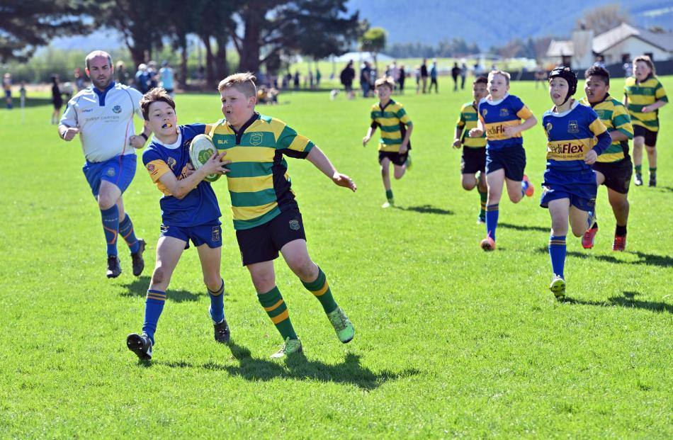 Rhys Johnstone (10), of Green Island, looks to score the try while Jackson Hucklebridge (11), of...