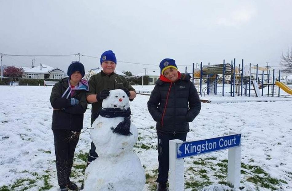 Lennox Beer, Vann Adams and Kalel Beer made a snowman at Moore Park in Milton. Photo: Jussy Beer-Williams