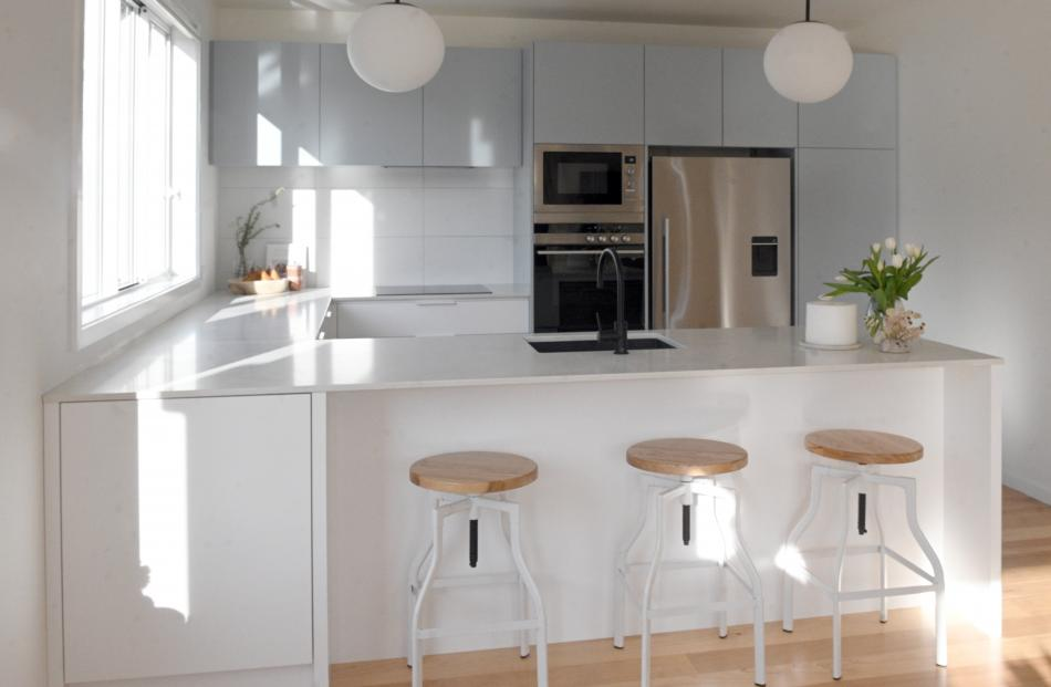 Pale blue cabinets provide soft colour in the otherwise white kitchen. Bifold windows over the...