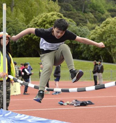 Genjin Gurung (9) flies over the high jump during the George Street Normal School's athletic...