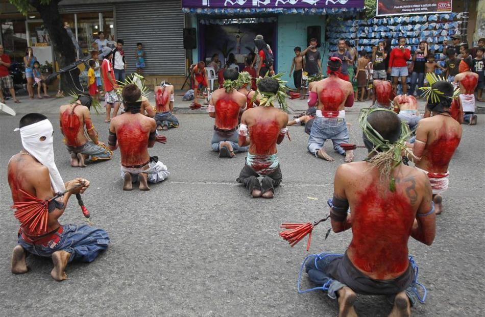 Hooded barefoot penitents perform self-flagellation to atone for their sins in San Fernando,...
