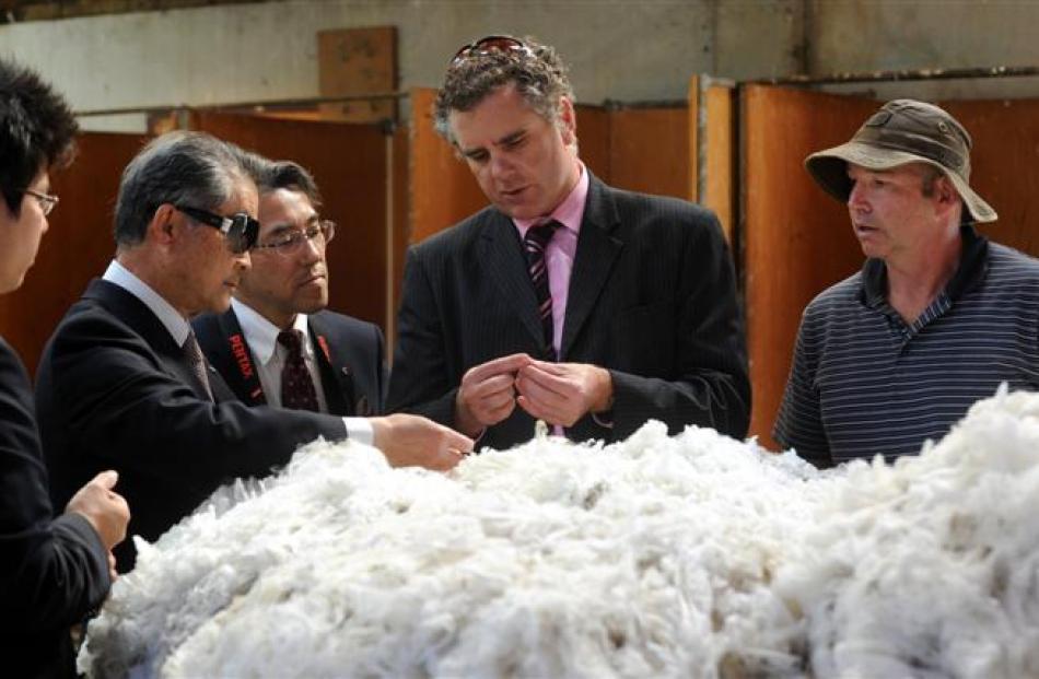 H. Dawson NZ senior trader Craig Smith shows (from left) Kento Nagao, Mitsuo Hori, and Kensuke...