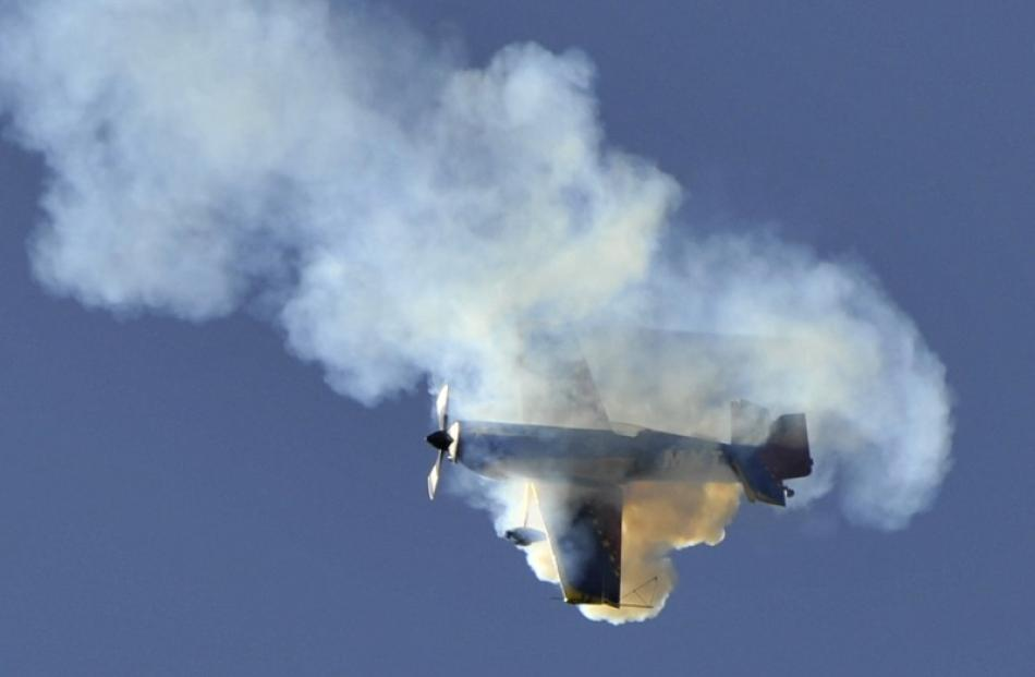 An MX2 aerobatic aircraft, flown by Doug Brooker, is shrouded in smoke as it performs a maneuver...