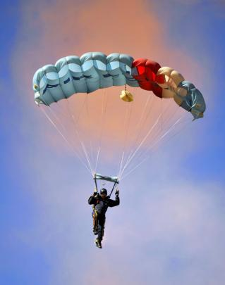 A member of the RNZAF's Kiwi Blue parachute team readys to land during Warbirds over Wanaka on...