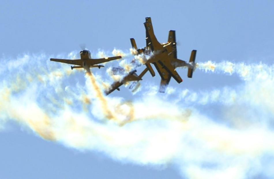 Aircraft from the RNZAF's Red Checkers perform a Spaghetti Break maneuver during Warbirds over...