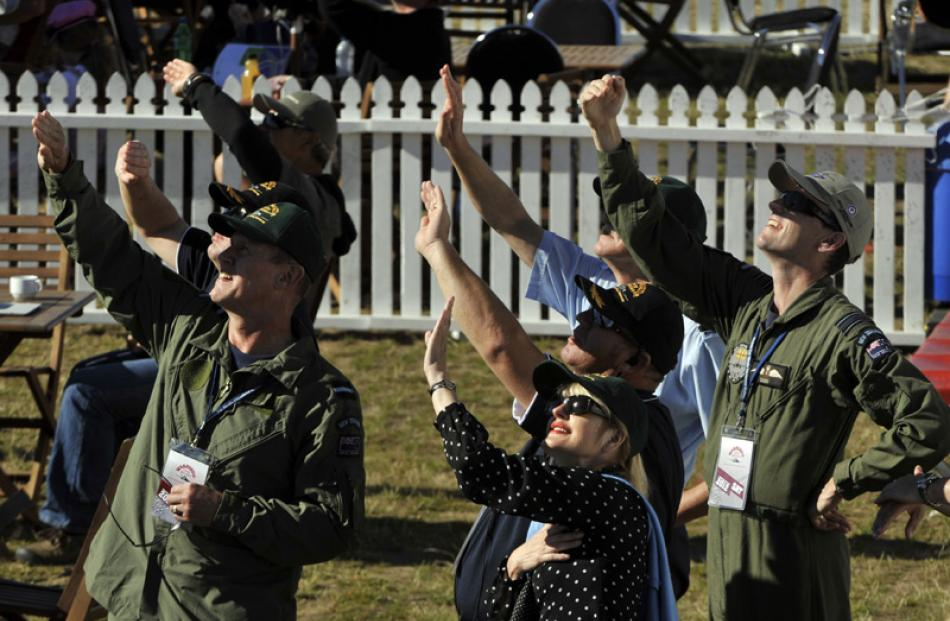 Members of the RNZAF shield themselves from the sun to get a better view of the action during...