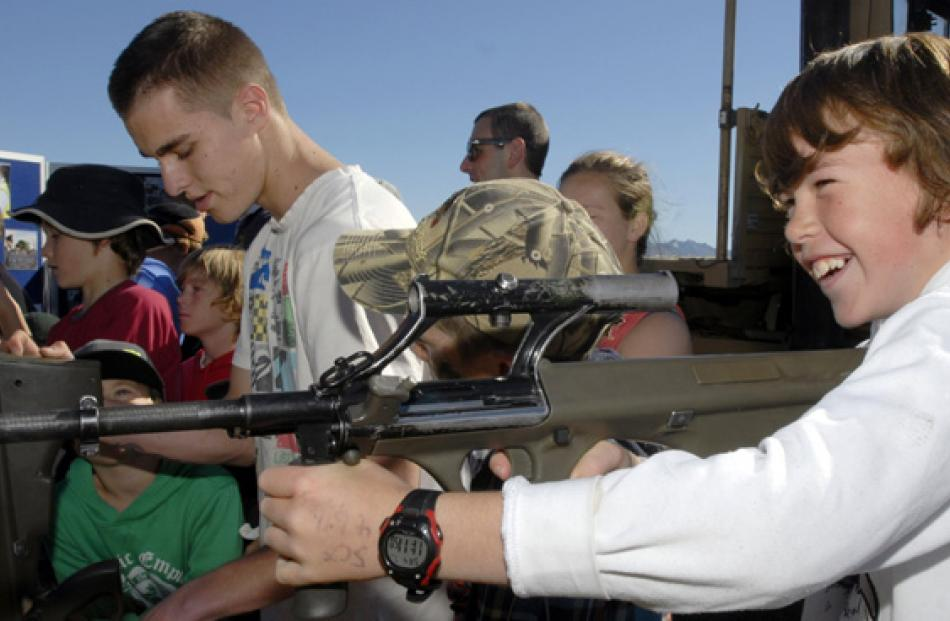 Tate Barron, of Dunedin, tries on a Steyr assault rifle for size at a NZ Defense Force display...