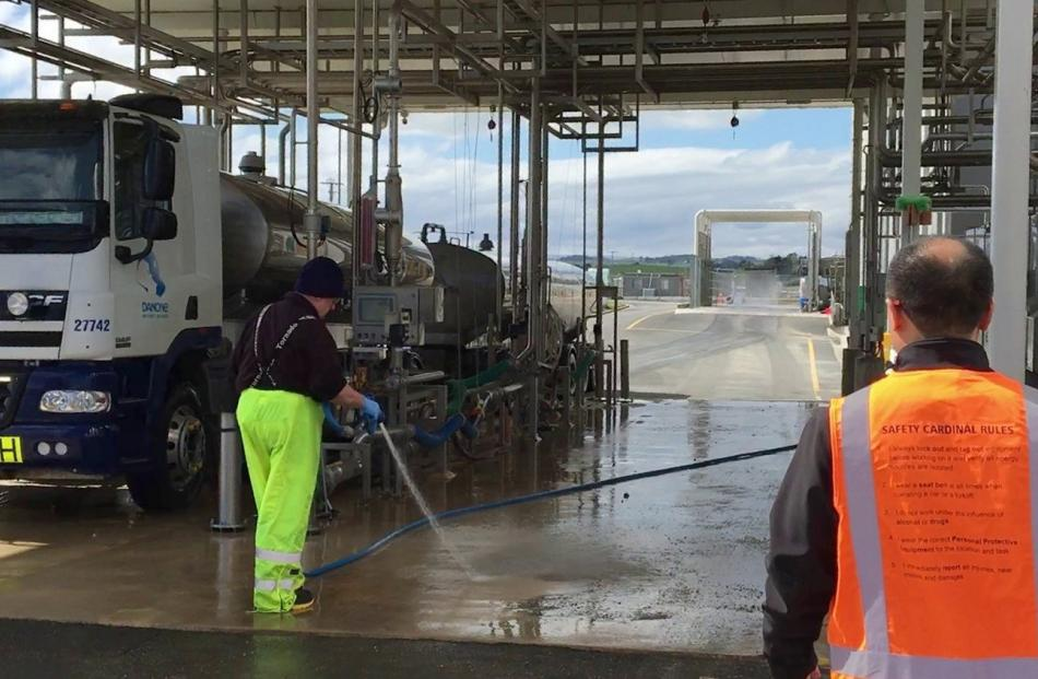 A driver cleans a milk delivery unit while operations director Leon Fung inspects the site.
