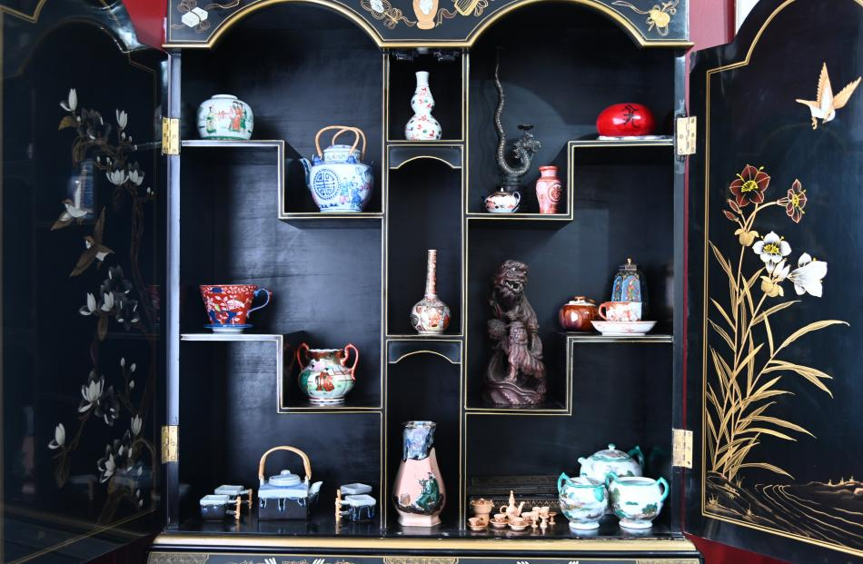 Miniatures are displayed in a painted cabinet. Right: A light inside the front door illuminates...