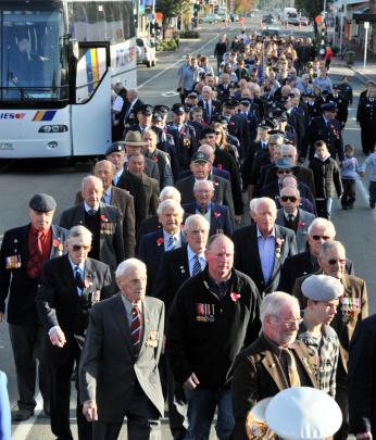 Returned servicemen march down Gordon Road before yesterday's Anzac Day service in Mosgiel.