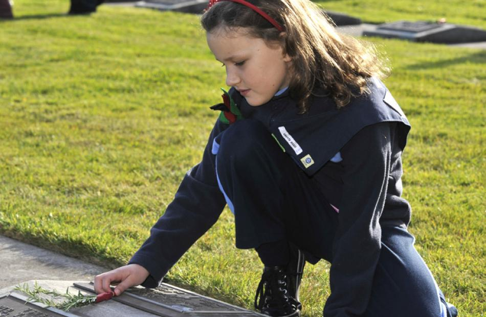 Sophie Wispinski (8), from Grants Braes Brownies, lays a posie on a soldiers grave at the...