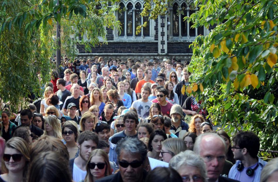 University staff and students parade along Memorial walk past the clocktower