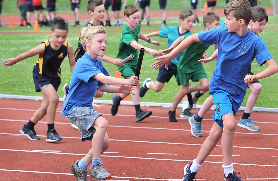 Jimmy Hinds passes the baton to Reuben Ure (both 9) for the Macandrew Bay School team in the boys...