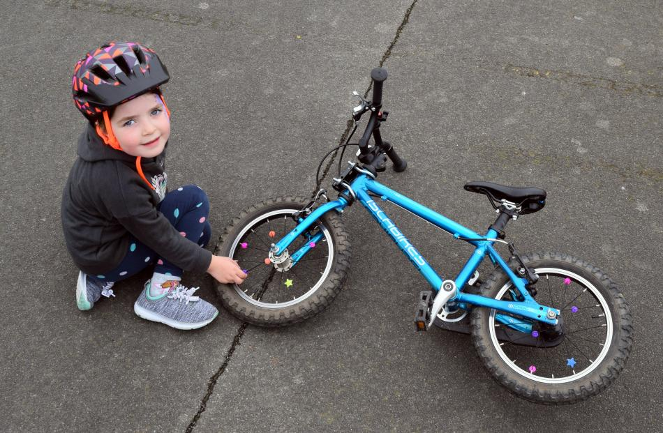 Zoe Hastings (4), of Sawyers Bay, decorates the spokes of her bike at the Family Bike Day. PHOTOS...
