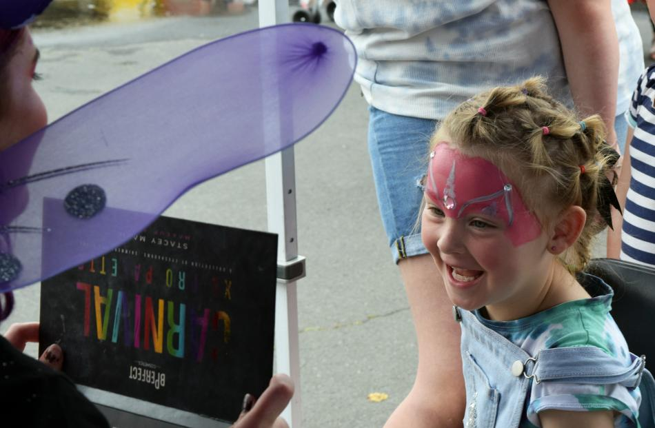Face painter Mel ''Fairy Spot'' Hall holds up a mirror to show Isobella Mahon (5), of St Kilda,...