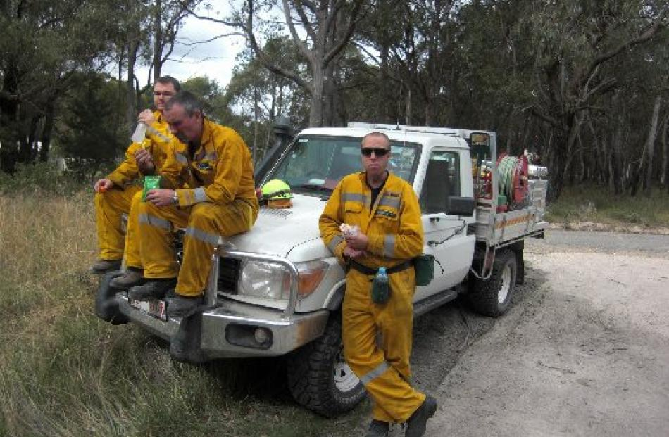 Doc rural firefighters Gavin Udy, Shayne Pearce and Glenn Fyfe take a break from a controlled...