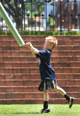 Max Collins (8), of Dunedin, throws a plastic caber during the celebrations.
