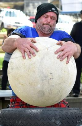 Danny Devine, of Kurow, impresses the crowd by lifting a 140kg Oamaru stone yesterday.