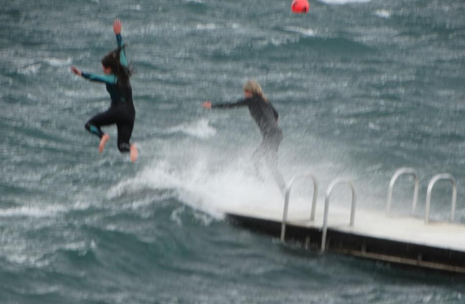 Young people leap from the swimming pontoon into the choppy waters of Lake Wanaka at Roys Bay...