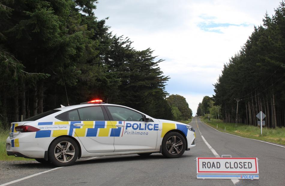 Police block a road after a falling tree brought down powerlines near Invercargill. PHOTO: ABBEY...
