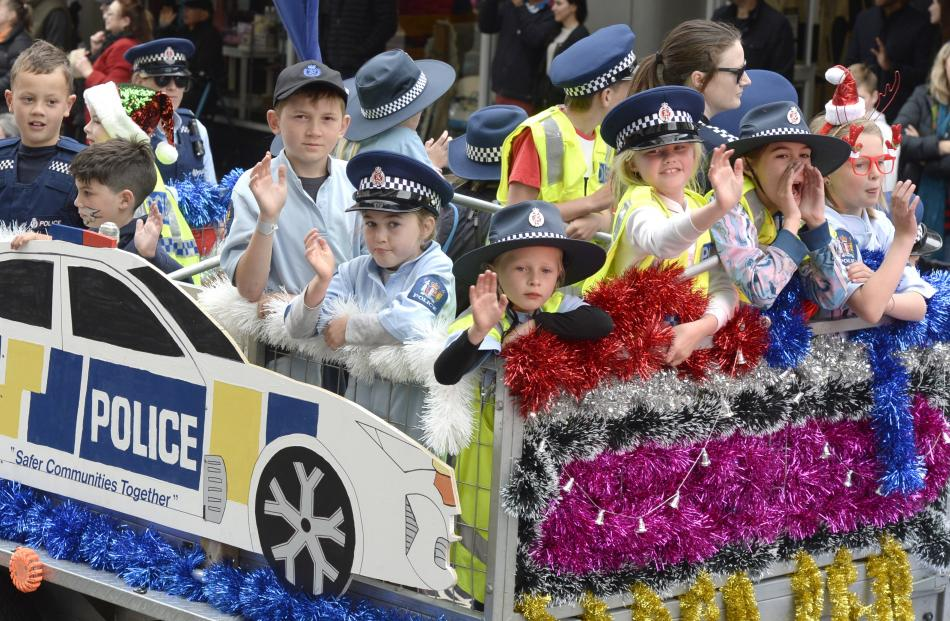 Children on board the Dunedin police float wave to the crowd as sirens wail.