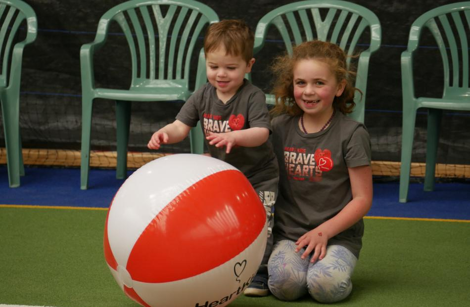 Siblings Cooper (2) and Sam McCook (7), of North East Valley, play with an inflatable ball....