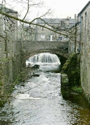 A picture-perfect scene of a waterfall in a village in the Yorkshire Dales.