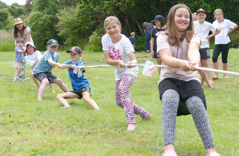 Visiting children take part in the tug-o-war event at the Papatowai Beach Carnival on New Year's...