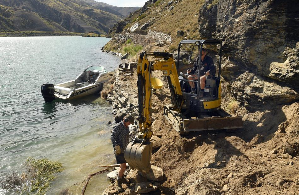 Brent Ward, of Lowburn, positions a rock under the watchful eye of Jake Schofield, of Timaru,...