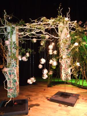 Glass bubbles filled with roses are suspended from bleached willow branches threaded with jasmine...