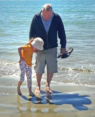 Kevin Hellyer and granddaughter Estelle Ross (4) paddle in the sea at Taramea Bay, Riverton....