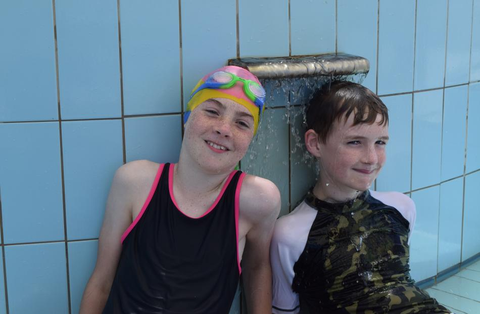 Cooling off at a water feature near the toddlers' pool are friends Nicola McMahon (11), of...