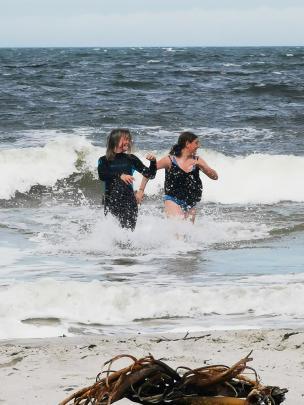 Jasmine Greer (13) and Kate Jordan (14) enjoy the surf at Brighton beach on January 13. PHOTO:...