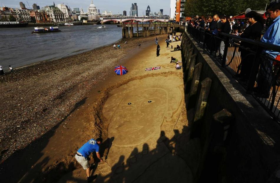A man creates an image of Britain's Queen Elizabeth in the sand on the banks of the River Thames....